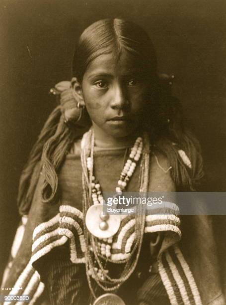 Jicarilla Apache girl halflength portrait wearing dress with buckskin cape several necklaces medallions her hair is tied on each side of her head...