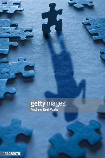 A jigsaw piece forms the shadow of a happy woman : Stock Photo