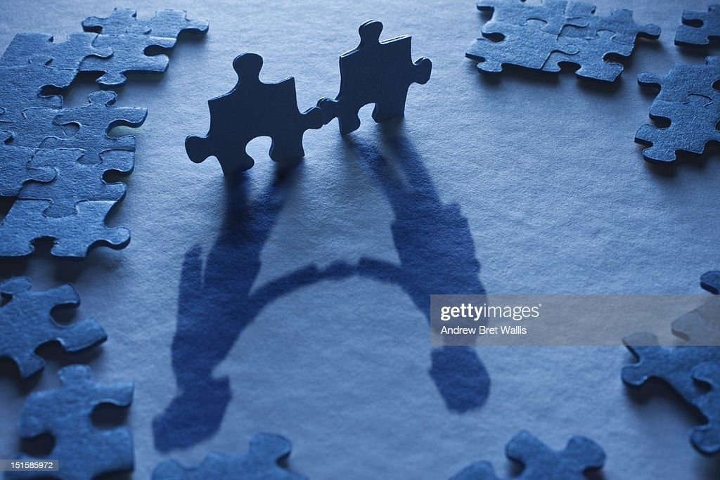 Jigsaw pieces form the shadow of a business deal : Stock Photo