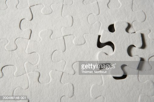 Jigsaw puzzle with one piece partially removed, overhead view : Stock Photo
