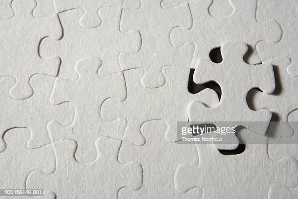 Jigsaw puzzle with one piece partially removed, overhead view