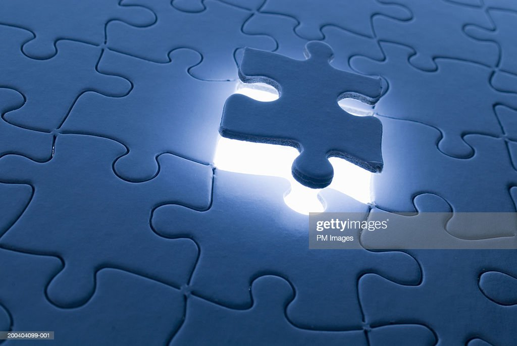 Jigsaw puzzle with piece floating (back lit) : Stock Photo