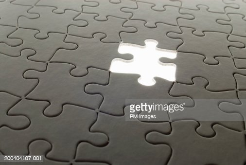 Jigsaw puzzle with piece floating : Stock Photo