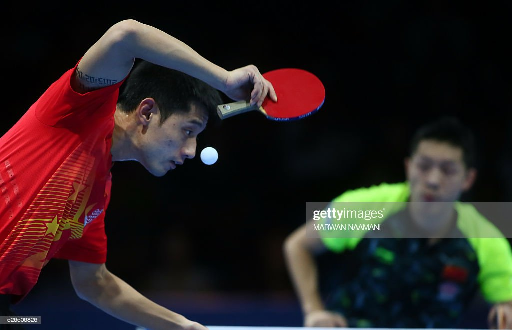 Jike Zhang of China returns the ball to his countryman Xin Xu during their men's singles semi-final table tennis match in the ITTF Nakheel Table Tennis Asian Cup, on April 30, 2016 in Dubai. / AFP / MARWAN