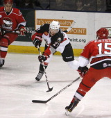 Portland Pirate Mark Voakes who scored the tying goal at the end of the first period is surrounded by Checkers Jon Matsumoto and Matthew Pistilli...