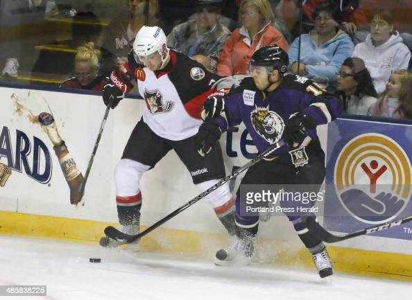 Portland TJ Brennan battles against the boards with Manchester Felix Schutz during first period action of the season opening game for the Portland...