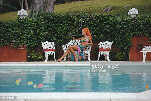 Jill Council relaxes with a drink by a swimming pool in Bermuda November 1969