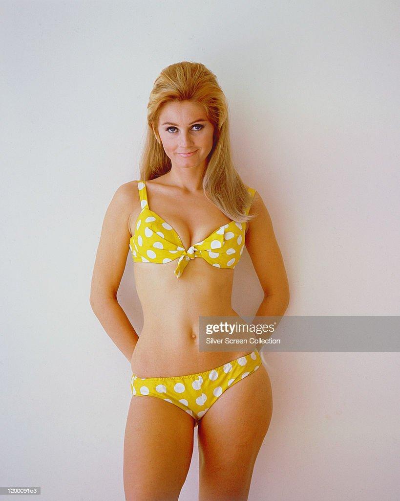 Jill Ireland (1936-1990), British actress, wearing a yellow polka dot bikini in a studio portrait, against a white background, circa 1960.
