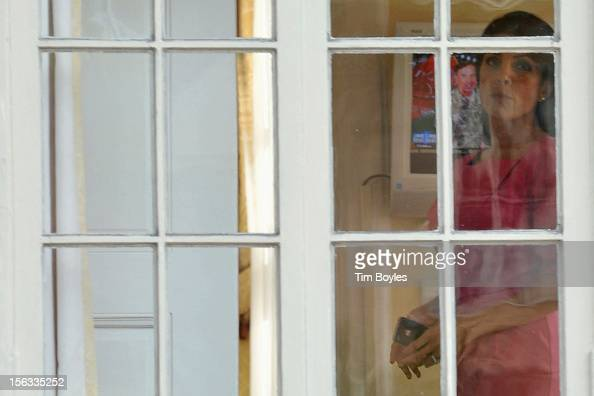 Jill Kelley looks out the window of her home as Gen David H Petraeus is seen on the television in the background on November 13 2012 in Tampa Florida...