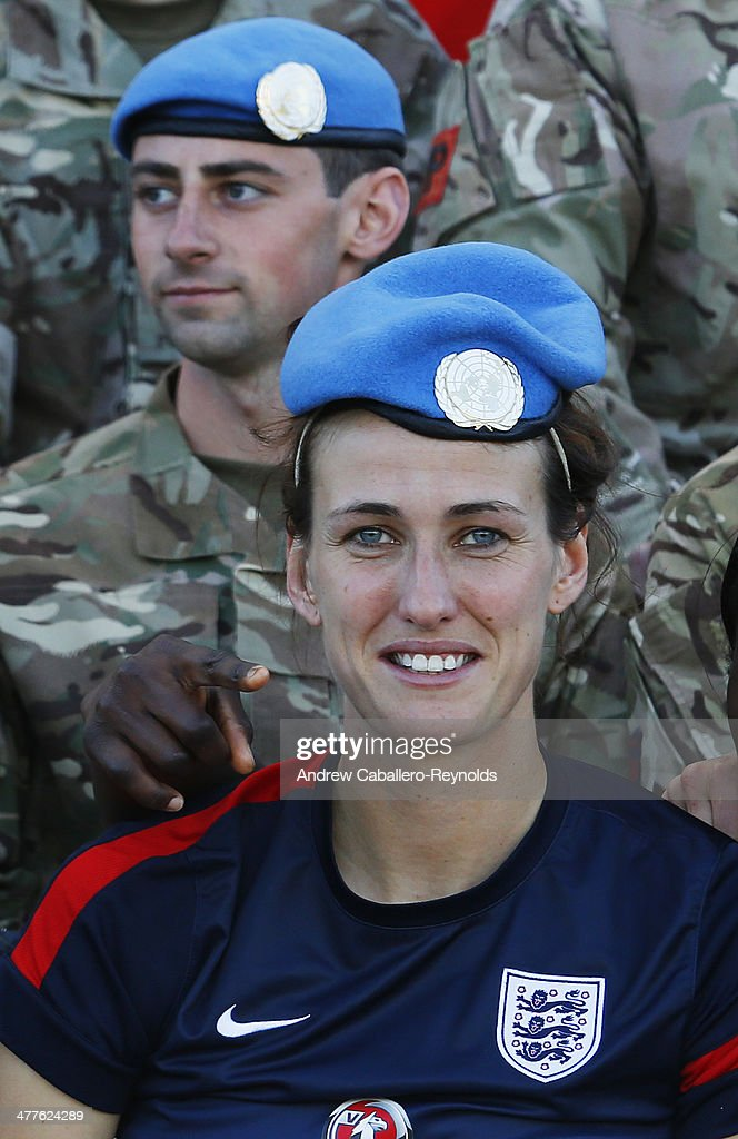 Jill Scott of England poses for a photo with UN Peacekeeprs from the UK after the Cyprus Cup match between England and Canada at GSP stadium on March 10, 2014 in Nicosia, Cyprus.