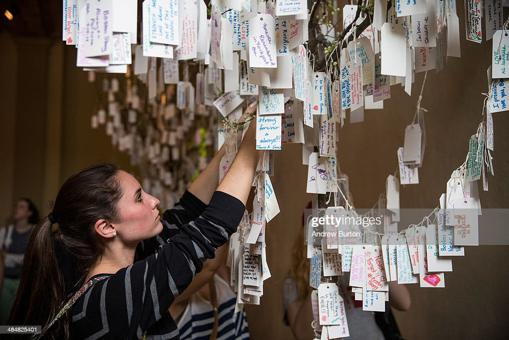 Jillian Munson, from Rochester, New York, hangs a hand-written message she wrote on a tree hung with messages inside a display titled, 'Dear Boston: Messages from the Marathon Memorial' in the Boston Public Library to commemorate the 2013 Boston Maraton bombings, on April 14, 2014 in Boston, Massachusetts. Last year, two pressure cooker bombs killed three and injured an estimated 264 others during the Boston marathon, on April 15, 2013.