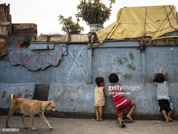 Jillian Reyes and a grade 1 elementary student draws a picture of a house on a wall near the shanty where she lives with her family beside the Estero...