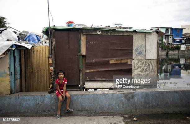 Jillian Reyes and a grade 1 elementary student sits in front of the shanty where she lives with her family beside the Estero de Vitas in Tondo in...