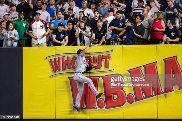 Jim Adduci of the Detroit Tigers makes an over the wall catch robbing Todd Frazier of the New York Yankees of a home run at Yankee Stadium on July 31...