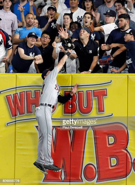 Jim Adduci of the Detroit Tigers prevents a home run with this catch over the wall in an MLB baseball game against the New York Yankees on July 31...