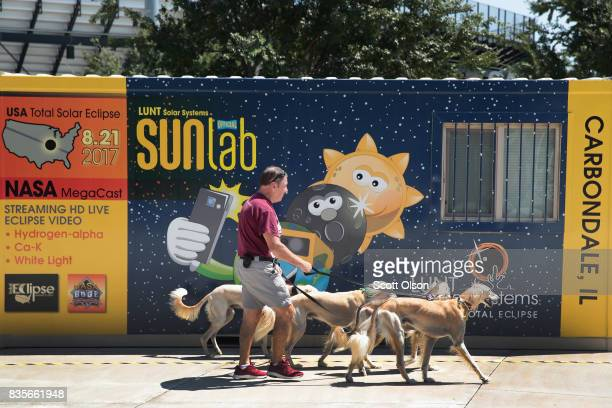 Jim Blair walks Saluki dogs past a solar eclipse exhibit on the campus of Southern Illinois University on August 19 2017 in Carbondale Illinois The...
