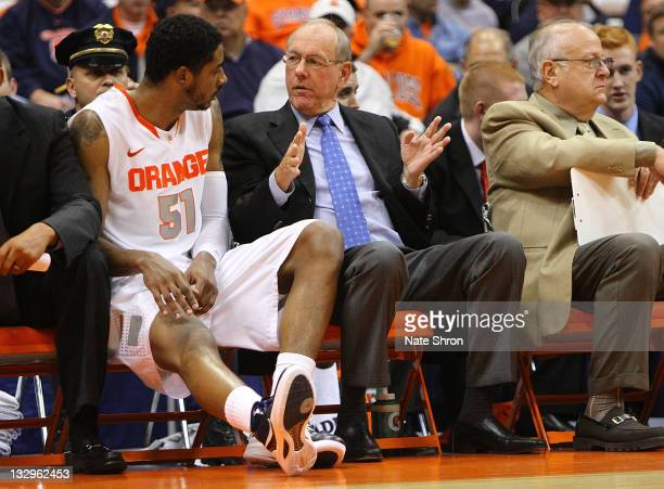 Jim Boeheim head coach of the Syracuse Orange talks with player Fab Melo on the bench during the game vs the Albany Great Danes during the NIT Season...