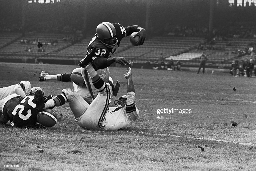 Jim Brown Cleveland Browns fullback goes diving over for a touchdown in third quarter on a three yard jaunt Attempting to stop Brown are Steelers'...