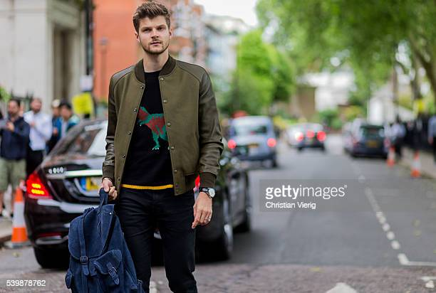 Jim Chapman wearing an olive college jacket and navy backpack outside Coach during The London Collections Men SS17 on June 13 2016 in London England