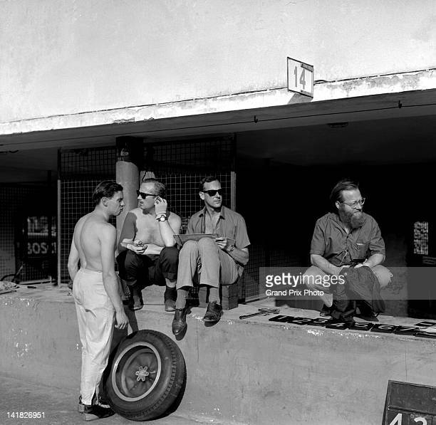 Jim Clark of Great Britain and driver of the Team Lotus Lotus 25 Climax V8 with team principal Colin Chapman a Lotus timekeeper and journalist Dennis...