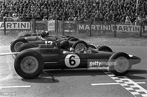 Jim Clark of Great Britain driving the Team Lotus Lotus 25 Climax V8 alongside Graham Hill in the Owen Racing Organisation BRM P57 BRM V8 and Bruce...
