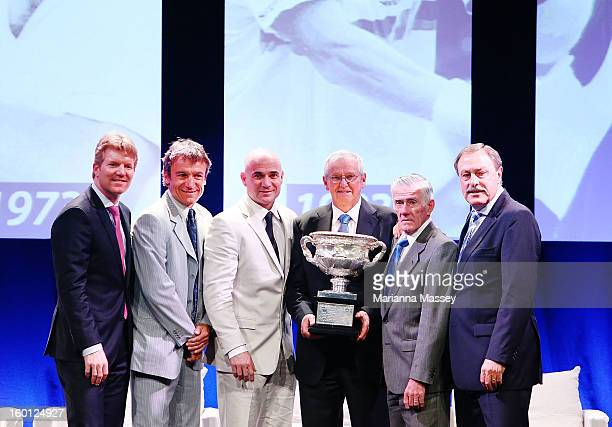 Jim Courier Mats Wilander Andre Agassi Roy Emerson Ken Rosewall and John Newcombe pose with the men's single trophy at the annual Legends' Lunch at...