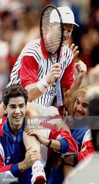 Jim Courier of the US is carried on the shoulders of his teammates Pete Sampras and Andre Agassi 06 December 1992 after Courier defeated...