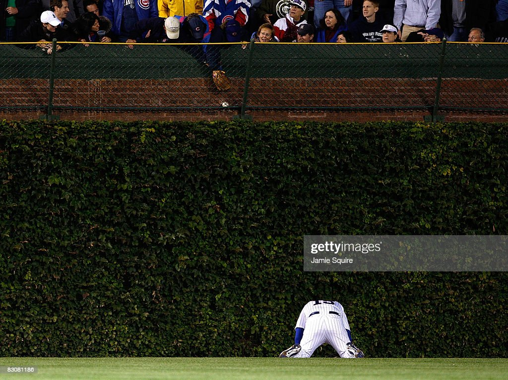 Jim Edmonds #15 of the Chicago Cubs looks down at the ground as fans reach over grab the home run ball hit by Russell Martin #55 of the Los Angeles Dodgers in the top of the ninth inning of Game One of the NLDS during the 2008 MLB Playoffs at Wrigley Field on October 1, 2008 in Chicago, Illinois. Russell home run was a solo shot to give the Dodgers a 7-2 lead.