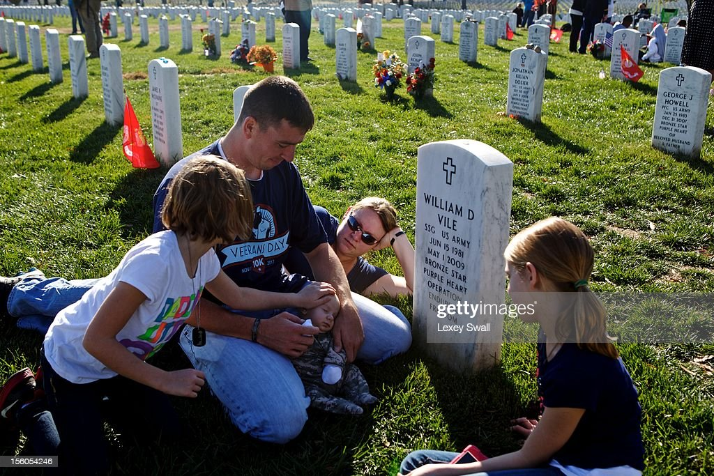 Jim Finnegan (L), his wife Carolyn and their children, Colleen, 7, Erin, 9, and William, 2 months, sit before the grave of Finnegan's best friend, Staff Sgt. William Vile who died in the war in Afghanistan in 2009, on Veteran's Day at Arlington National Cemetery on November 11, 2012 in Arlington, Virginia. Fiinnegan named his son after his friend who he had known since he was 14 years old. Numerous events are under across the country to honor the nation's current and former service members.