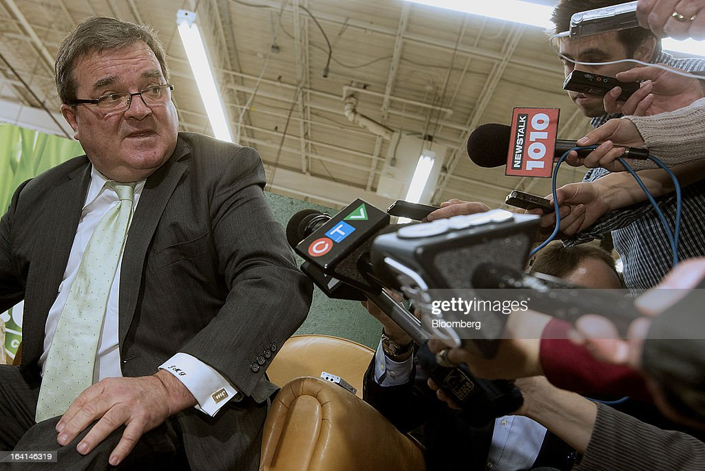 Jim Flaherty, Canada's finance minister, center, speaks to the media while trying on shoes to purchase, a pre-budget tradition, at the Roots Ltd. manufacturing facility in Toronto, Ontario, Canada, on Wednesday, March 20, 2013. Flaherty said his budget tomorrow will seek to balance the need for sound government finances with growth-promoting steps, including measures to help the nation's manufacturers. Photographer: Norm Betts/Bloomberg via Getty Images