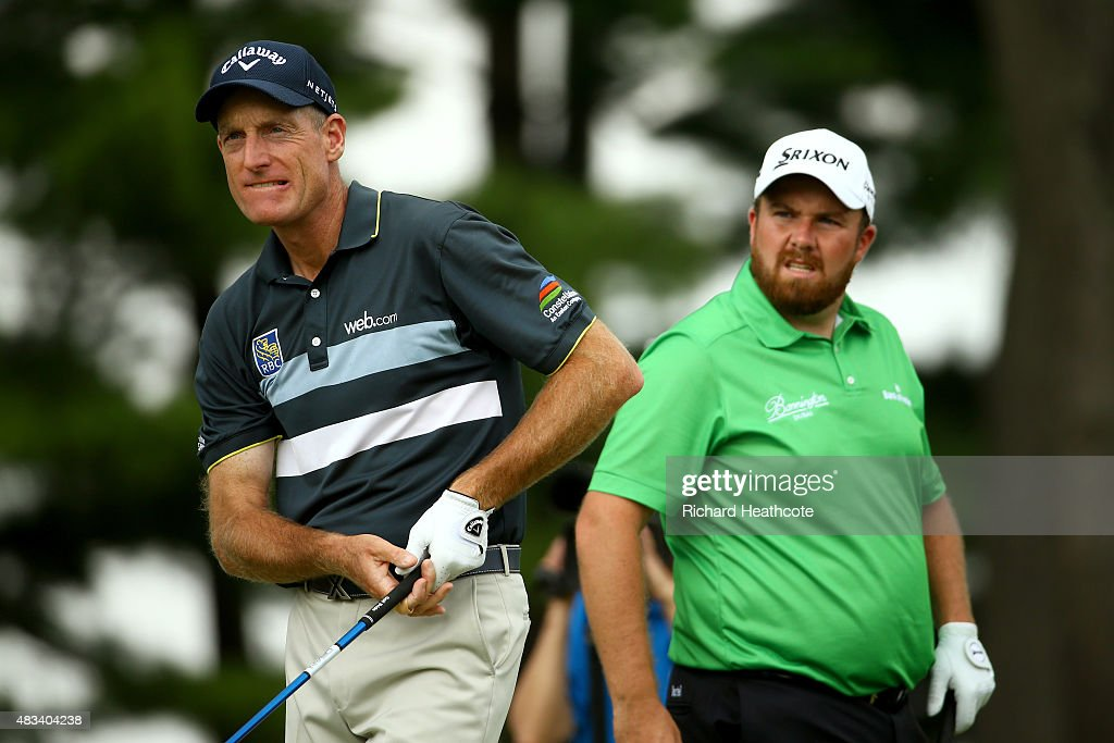 Jim Furyk hits off the fourth tee as Shane Lowry of Ireland looks on during the third round of the World Golf Championships - Bridgestone Invitational at Firestone Country Club South Course on August 8, 2015 in Akron, Ohio.