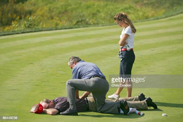 Jim Furyk of the US team is treated by a trainer during the first round of The Presidents Cup at Robert Trent Jones Golf Club in Prince William...
