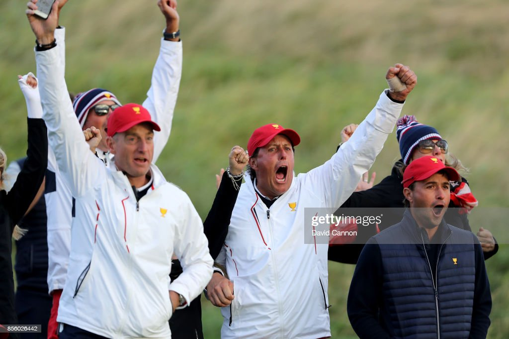 Jim Furyk, Phil Mickelson and Kevin Kisner of the United States team (L-R) react to Charley Hoffman's chip-in birdie at the 17th hole during the Saturday afternoon fourball matches in the 2017 Presidents Cup at the Liberty National Golf Club on September 30, 2017 in Jersey City, New Jersey.