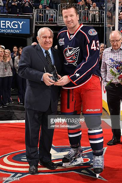 Jim Gregory NHL Senior Vice President of Hockey Operations presents an NHL Tiffany Crystal to Scott Hartnell in recognition for playing 1000 games in...