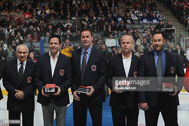 Jim Gregory stands beside Doug Gilmour Joe Nieuwendyk Mark Howe and Ed Belfour who show off their Hall of Fame jackets prior to a Legends of Hockey...