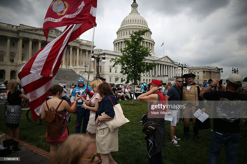 Jim Griffin (L), dressed as Capt. America and James Manship (R), dressed as George Washington greet people while participating in a Tea Party rally at the U.S. Capitol, June 19, 2013 in Washington, DC. The group Tea Party Patriots hosted the rally to protest against the Internal Revenue Service's targeting Tea Party and grassroots organizations for harassment.