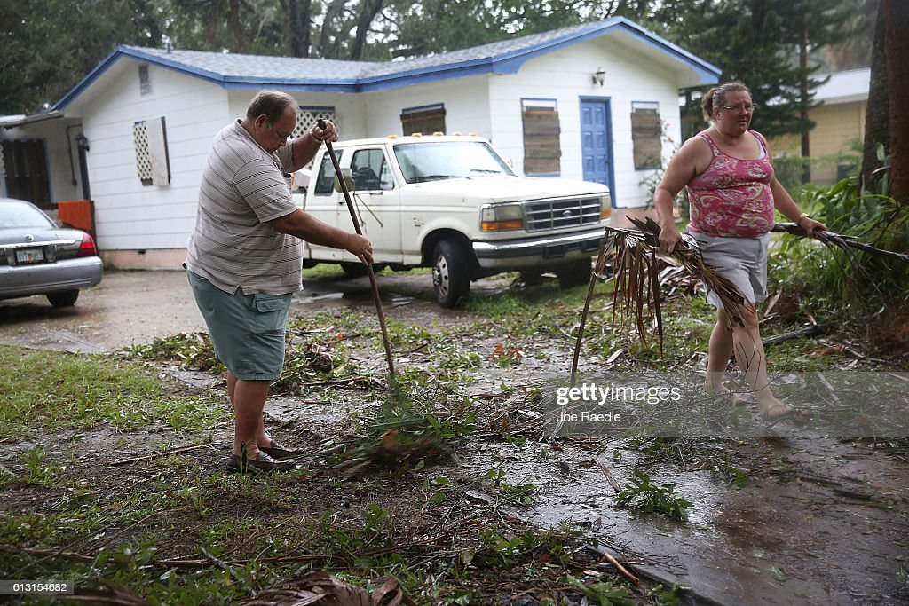 Jim Griggis and Marlin Whaley clean up after Hurricane Matthew passed through the area on October 7 2016 in Fort Pierce Florida The hurricane is...