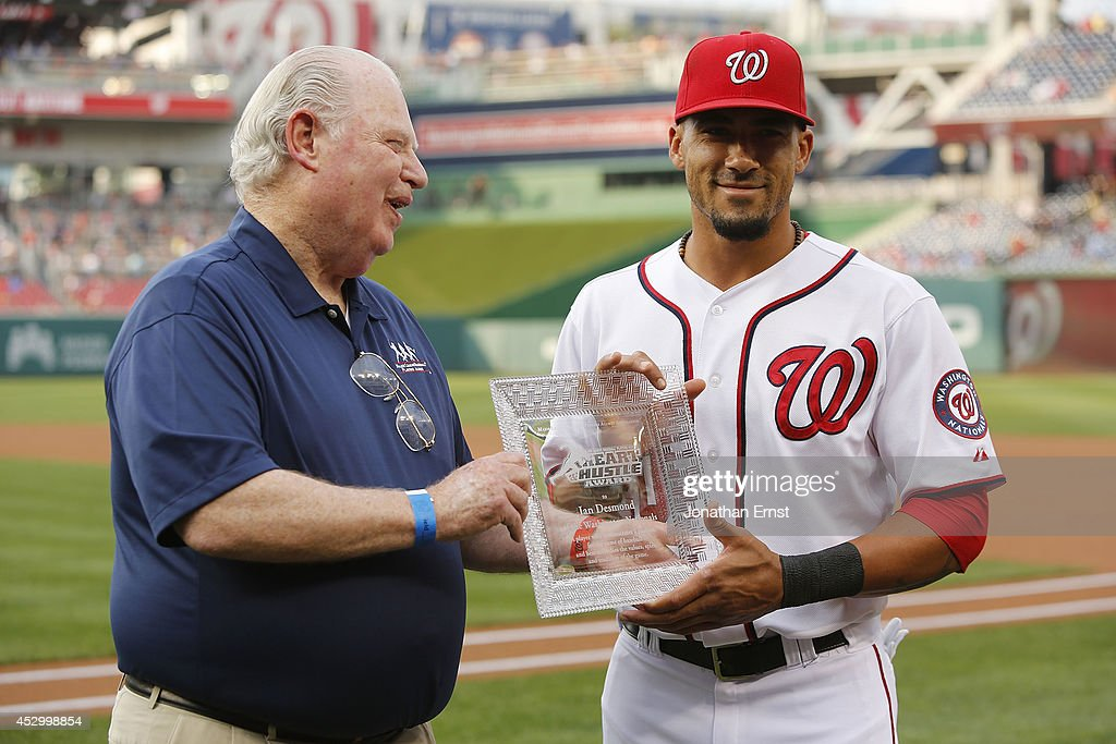 Jim Hannan (L), representing the Major League Baseball Players Alumni Association, presents the group's Heart and Hustle Award to shortstop Ian Desmond #20 of the Washington Nationals before their game against the Philadelphia Phillies at Nationals Park on July 31, 2014 in Washington, DC.