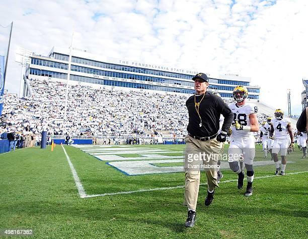 Jim Harbaugh head coach of the Michigan Wolverines runs onto the field prior to the game against the Penn State Nittany Lions at Beaver Stadium on...