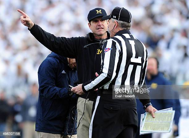 Jim Harbaugh head coach of the Michigan Wolverines talks to an official during the game against the Penn State Nittany Lions at Beaver Stadium on...