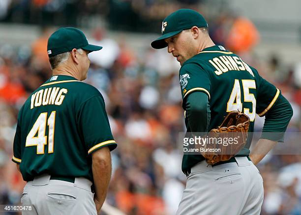 Jim Johnson of the Oakland Athletics talks with pitching coach Curt Young during the sixth inning of a game against the Detroit Tigers at Comerica...