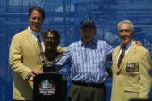 Jim Kelly stands next to his bust with Ralph Wilson owner of the Buffalo Bills and his presenter and former head coach Marv Levy after his induction...