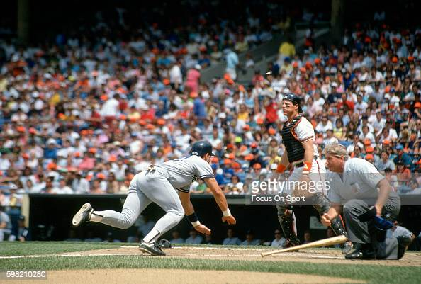 Jim Leyritz of the New York Yankees scores diving into home plate against the Baltimore Orioles during an Major League Baseball game circa 1990 at...
