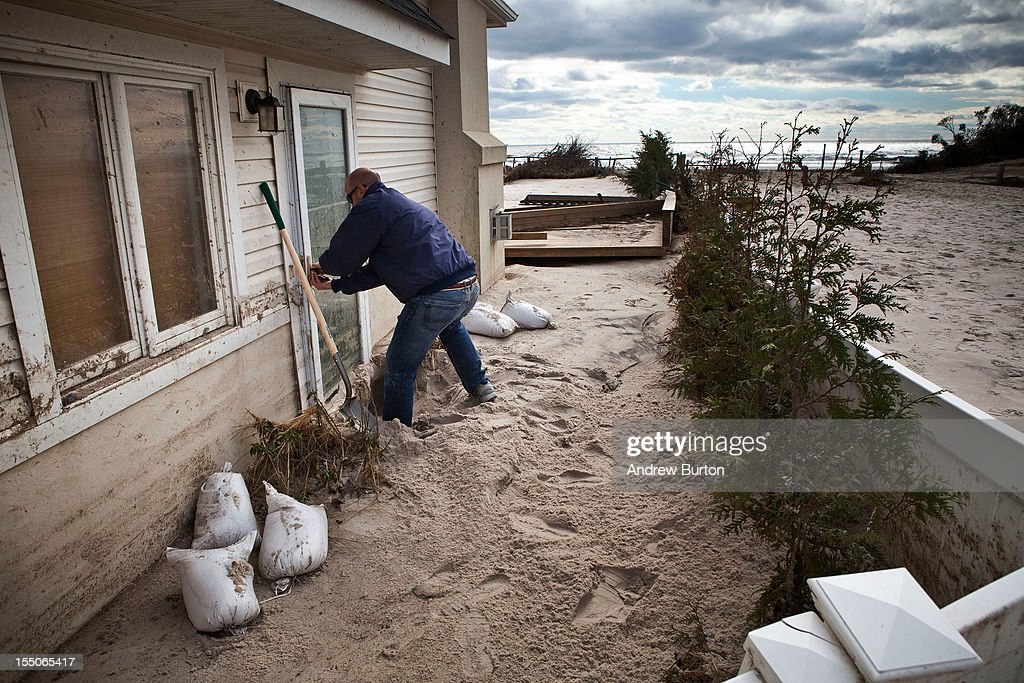 Jim Margiotta attempts to open the front door of his house, which was flooded with ocean water and sand by Hurricane Sandy, on October 31, 2012 in Long Beach, New York.The storm has claimed many lives in the United States and has caused massive flooding across much of the Atlantic seaboard. U.S. President Barack Obama has declared the situation a 'major disaster' for large areas of the U.S. east coast, including New York City, with widespread power outages and significant flooding in parts of the city.