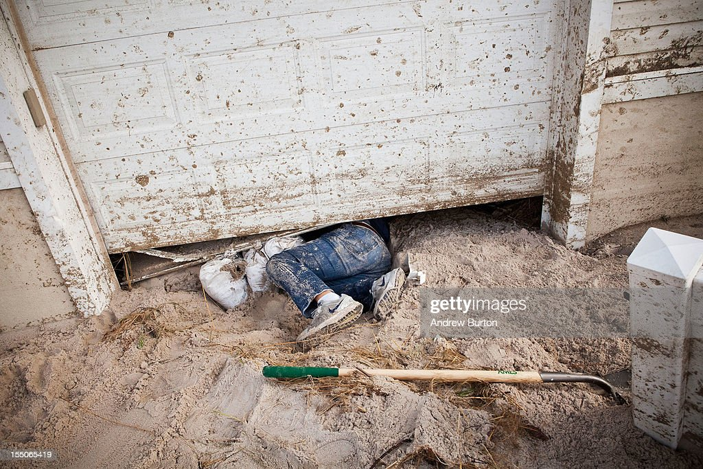 Jim Margiotta climbs under his garage door which was flooded with ocean water and sand by Hurricane Sandy on October 31 2012 in Long Beach New...