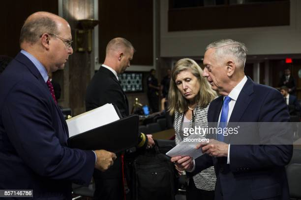 Jim Mattis US secretary of defense right speaks to aides after testifying during a Senate Armed Forces Committee hearing in Washington DC US on...