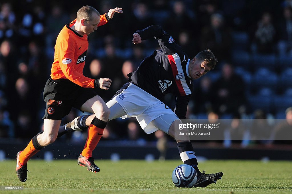 Jim McAlister of Dundee battles with Willo Flood of Dundee United during the Clydesdale Bank Premier League match between Dundee and Dundee United at Dens Park Stadium on December 9, 2012 in Dundee, Scotland.