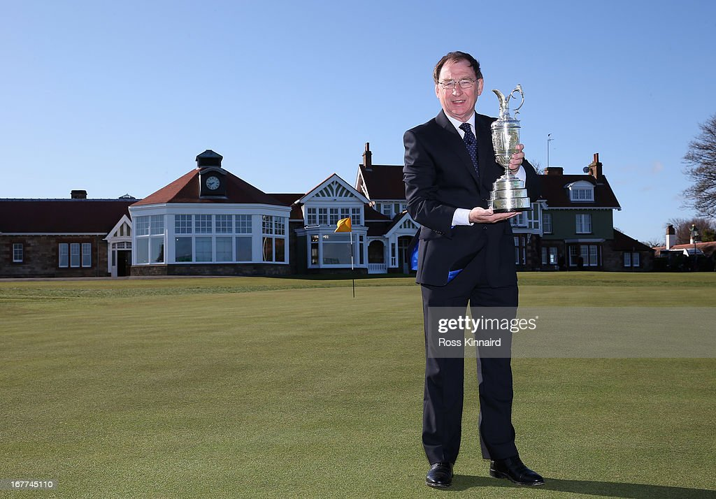 Jim McArthur of Scotland the Chairman of the R&A Championship Committee with The Open Championship trophy beside the 18th green in front of the clubhouse during The Open Championship media day at Muirfield on April 29, 2013 in Gullane, Scotland.