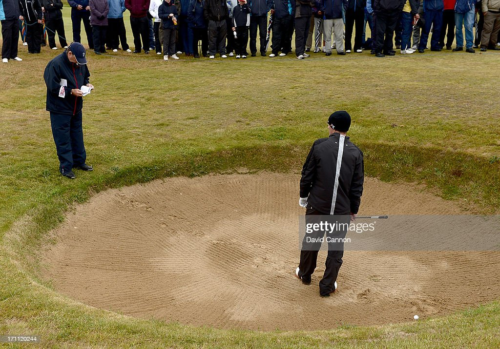 Jim McArthur the match referee checking the rules where Garrick Porteous of England played his second shot on the second hole where the ball rebounded and struck him on the shoulder off the face of the bunker leading to an automatic loss of the hole during the afternoon round in the final of the 2013 Amateur Championship at Royal Cinque Ports Golf Club on June 22, 2013 in Deal, England.