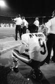 Jim McMahon of the Chicago Bears sits on the sideline during the game against the Miami Dolphins at the Orange Bowl on December 2 1985 in Miami...